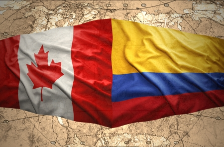Waving Colombian and Canadian flags on the of the political map of the world photo