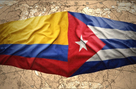 Waving Colombian and Cuban flags on the of the political map of the world photo