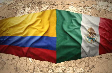 Waving Colombian and Mexican flags on the of the political map of the world photo