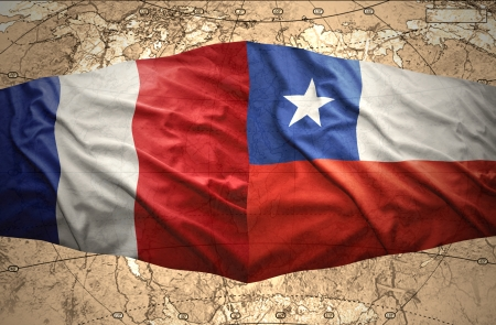 Waving Chilean and French flags on the of the political map of the world photo
