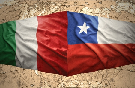 Waving Chilean and Italian flags on the of the political map of the world photo