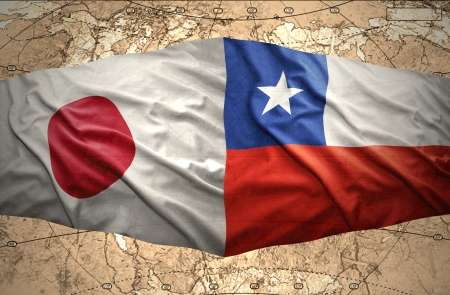 Waving Chilean and Japanese flags on the of the political map of the world photo