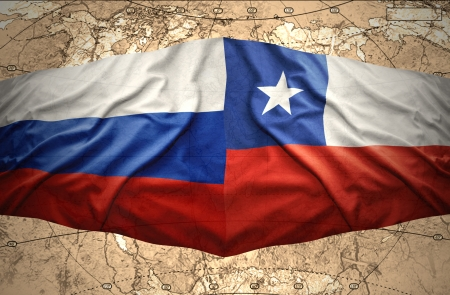 Waving Chilean and Russian flags on the of the political map of the world photo