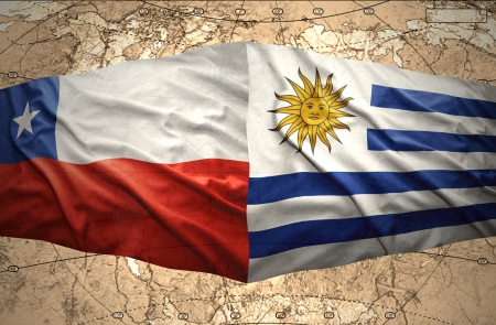 Waving Chilean and Uruguayan flags on the of the political map of the world photo
