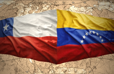 Waving Chilean and Venezuelan flags on the of the political map of the world photo