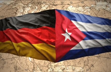 Waving Cuban and German flags on the of the political map of the world photo
