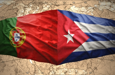 Waving Cuban and Portuguese flags on the of the political map of the world photo