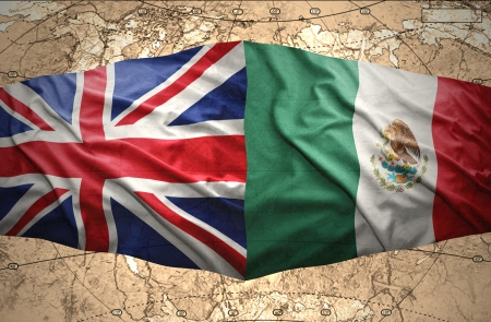 Waving Mexican and British flags on the of the political map of the world Stock Photo
