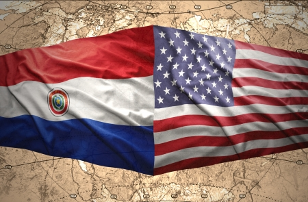 Waving Paraguayan and American flags on the of the political map of the world photo