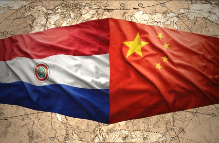 Waving Paraguayan and Chinese flags on the of the political map of the world photo