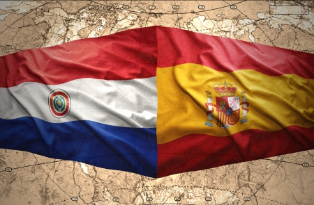 Waving Paraguayan and Spanish flags on the of the political map of the world photo