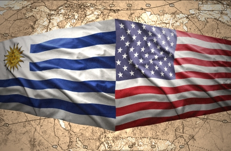 Waving Uruguayan and American flags on the of the political map of the world photo