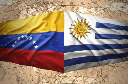 Waving Uruguayan and Venezuelan flags on the of the political map of the world photo
