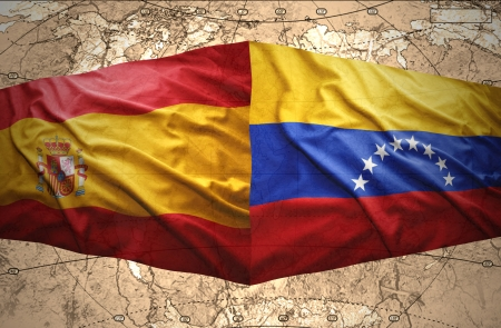 Waving Venezuelan and Spanish flags on the of the political map of the world photo