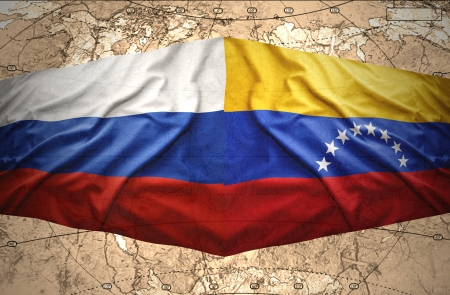 Waving Venezuelan and Russian flags on the of the political map of the world photo