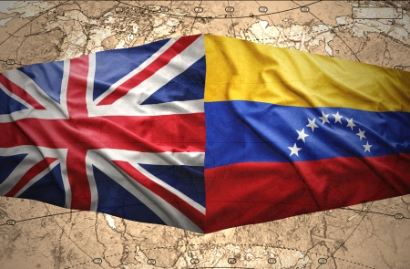 Waving Venezuelan and British flags on the of the political map of the world photo