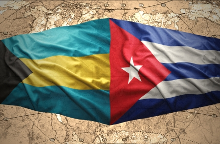 Waving Bahamian and Cuban flags on the of the political map of the world photo