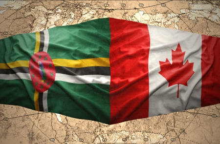 Waving Dominica and Canadian flags on the of the political map of the world photo