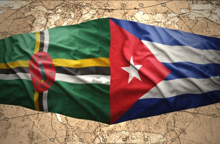 Waving Dominica and Cuban flags on the of the political map of the world photo