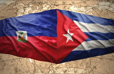 Waving Haitian and Cuban flags on the of the political map of the world photo