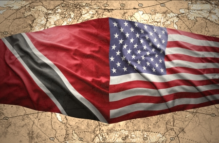 Waving Trinidadian and American flags on the of the political map of the world photo
