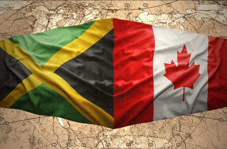 Waving Jamaican and Canadian flags on the of the political map of the world photo