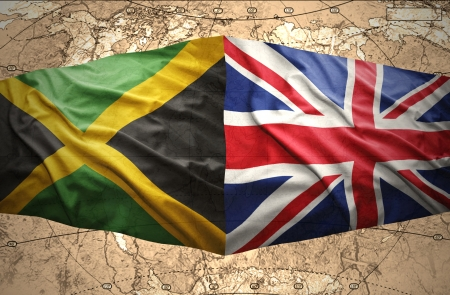 Waving Jamaican and British flags on the of the political map of the world photo