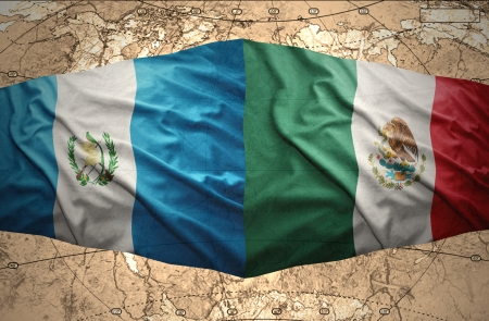 Waving Guatemalan and Mexican flags on the of the political map of the world photo