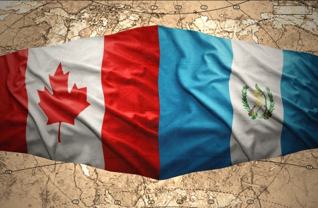 Waving Guatemalan and Canadian flags on the of the political map of the world photo