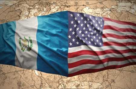 Waving Guatemalan and American flags on the of the political map of the world