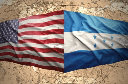 Waving Honduran and American flags on the of the political map of the world photo