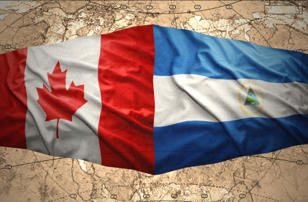 nicaraguan: Waving Nicaraguan and Canadian flags on the of the political map of the world