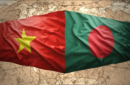 Waving Vietnamese and Bangladesh flags of the political map of the world photo