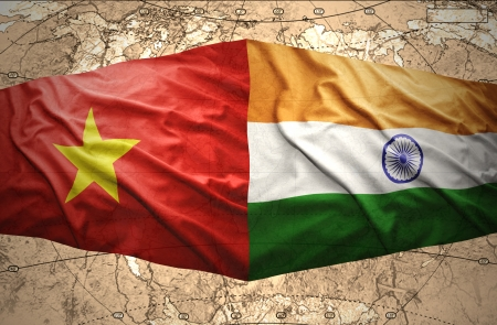 Waving Vietnamese and Indian flags of the political map of the world photo