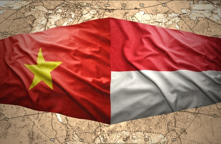 Waving Vietnamese and Indonesian flags of the political map of the world photo