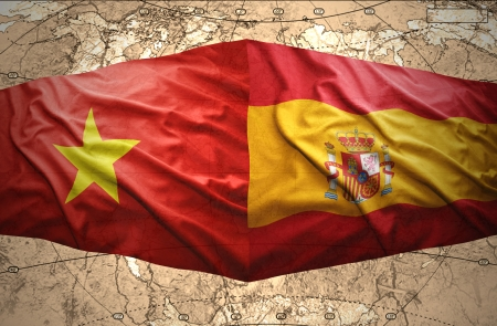 Waving Vietnamese and Spanish flags of the political map of the world photo