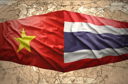 Waving Vietnamese and Thai flags of the political map of the world photo