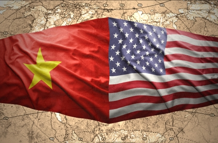 Waving Vietnamese and American flags of the political map of the world photo