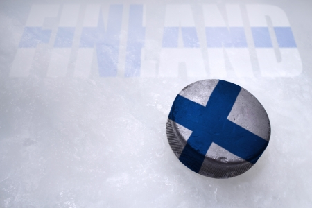 Vintage old hockey puck with the Finland flag is on the ice