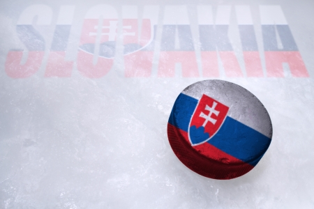Vintage old hockey puck with the Slovakia flag is on the ice photo