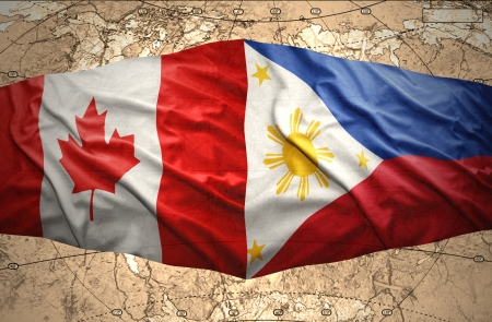 Waving Philippine and Canadian flags of the political map of the world photo
