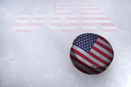 Vintage old hockey puck with the United States of America flag is on the ice photo