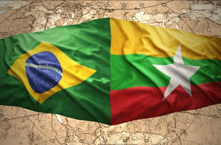 Waving Myanmar and Brazilian flags of the political map of the world photo