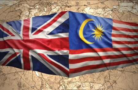 Waving Malaysian and British flags of the political map of the world photo