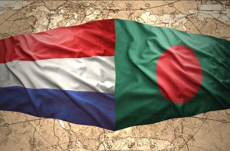 Waving Bangladesh and Dutch flags of the political map of the world photo