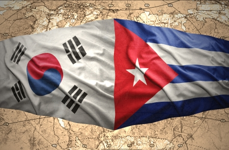 Waving Korean and Cuban flags of the political map of the world photo