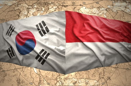 Waving Korean and Indonesian flags of the political map of the world photo