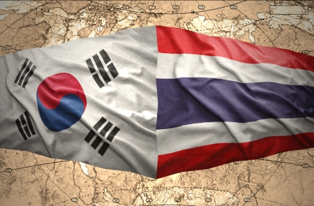 Waving Korean and Thai flags of the political map of the world photo