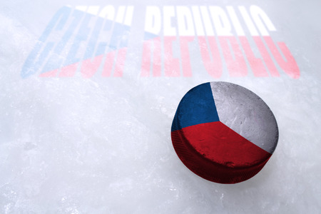 Vintage old hockey puck with the Czech Republic flag is on the ice photo