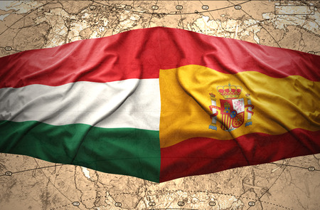 Waving Hungarian and Spanish flags of the political map of the world photo